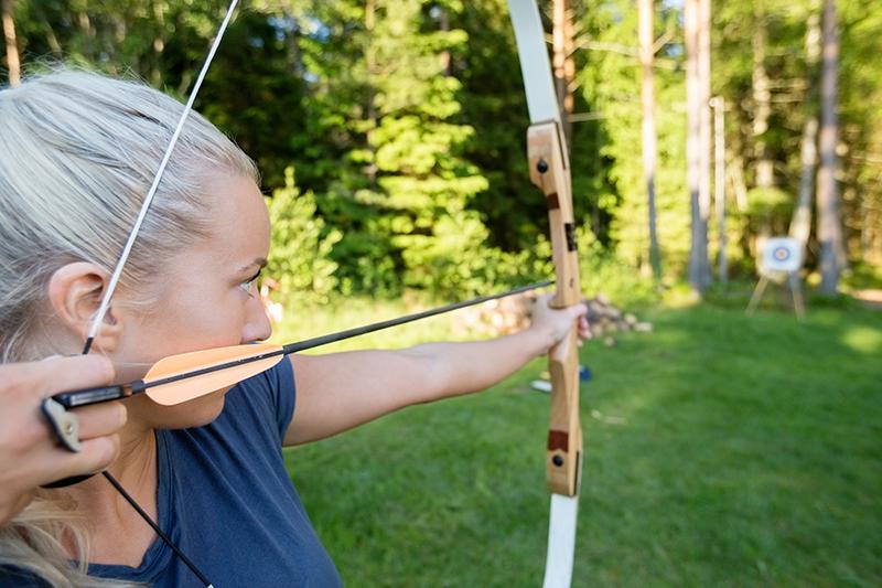 Kvinde skyder med bue og pil til teambuilding.