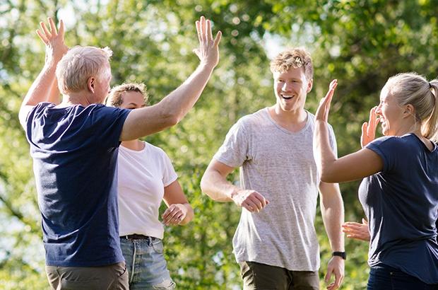 Glade kollegaer giver high fives. Sommer og sol i skoven med målrettet og underholdende teamudvikling.