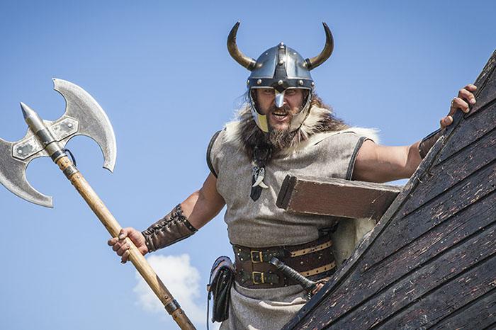 Mand med skæg, hjelm og økse er udklædt som viking til anderledes teambuilding.