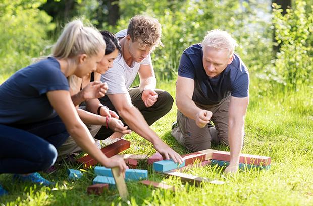 4 mennesker laver kommunikationsøvelser til teambuilding i skoven.