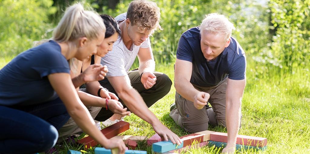hvad er samarbejde   4 mennesker laver en samarbejdsøvelse i skoven