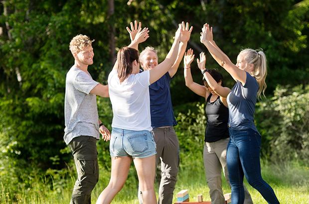 5 mennesker fejrer et succesfuldt samarbejde til teambuilding i skoven.