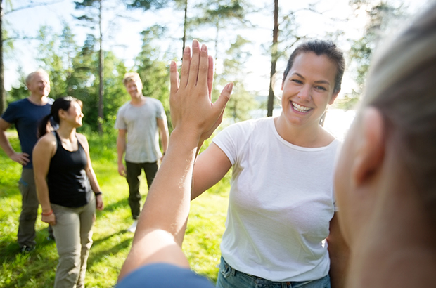 Glade mennesker i skoven. To kollegaer fejrer en god og sjov samarbejdsøvelse med en high five.