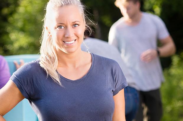 Glad, lyshåret kvinde i skoven med kollegaer