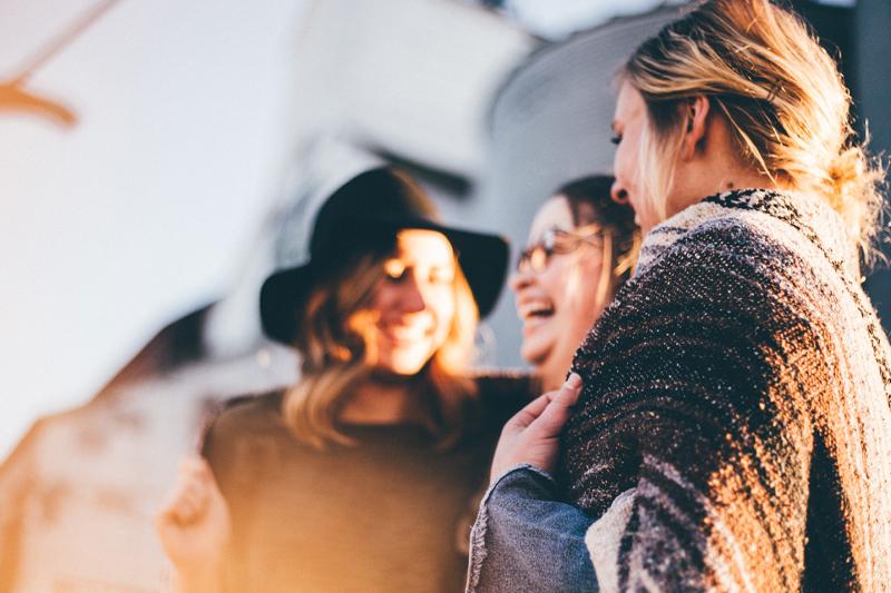 Tre kvinder griner til teambuilding.