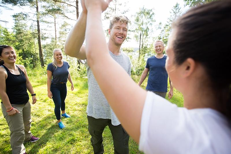 Fem mennesker giver high five til teambuilding.