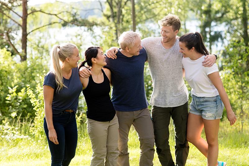 Fem glade mennesker til et teambuilding arrangement.