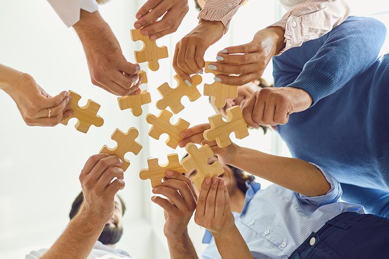 Mennesker samarbejder med brikker til teambuilding.