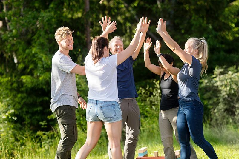 Fem kollegaer jubler til udendørs teambuilding på Sjælland.